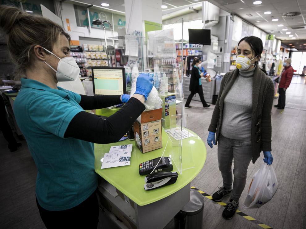 Una clienta compra una mascarilla, ayer en la farmacia Artal Centro de Zaragoza