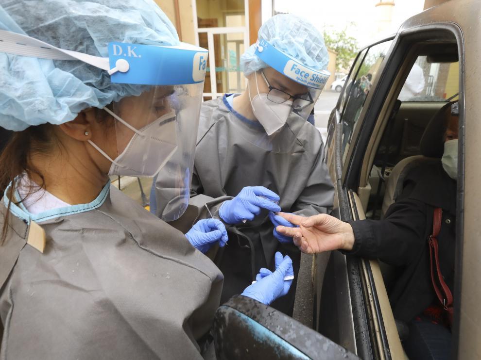 Dos sanitarios toman una muestra de sangre para un test rápido de coronavirus en el Hospital Provincial de Huesca.