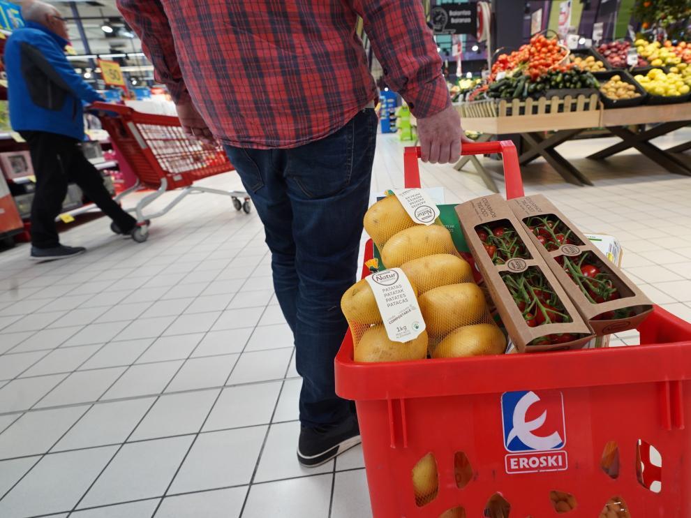 Dos de los envases de ecodiseño de la marca: tomate cocktail romántico Eroski Natur y malla y etiqueta compostable de las patatas Eroski Natur.