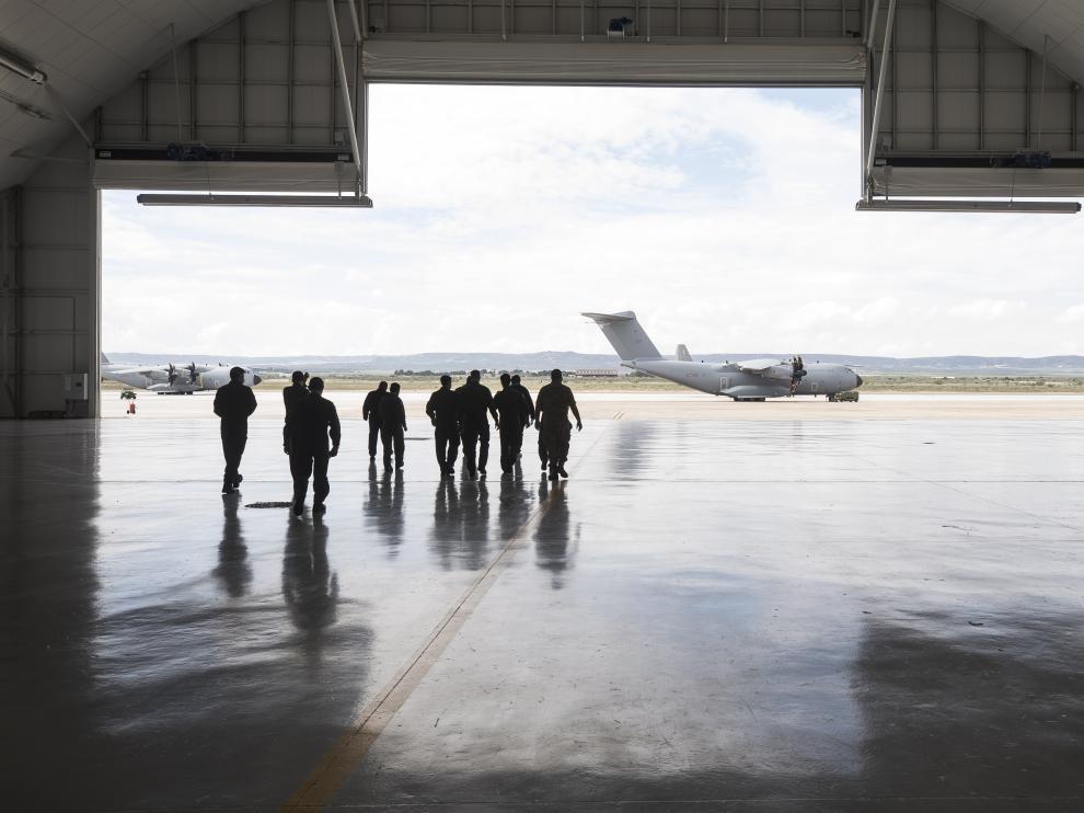 Los pilotos de aviones del Ala 31, protegidos con mascarillas y guantes, salen del hangar hacia la plataforma de la Base Aérea de Zaragoza.