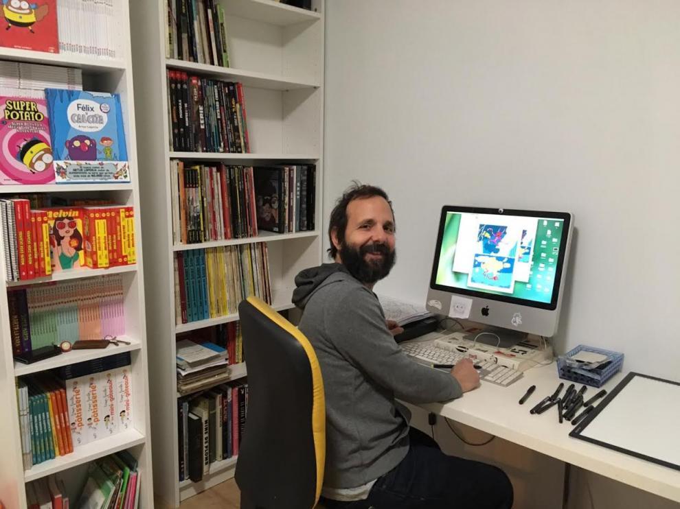 El ilustrador Artur Laperla, en su mesa de trabajo, junto a parte de su biblioteca.
