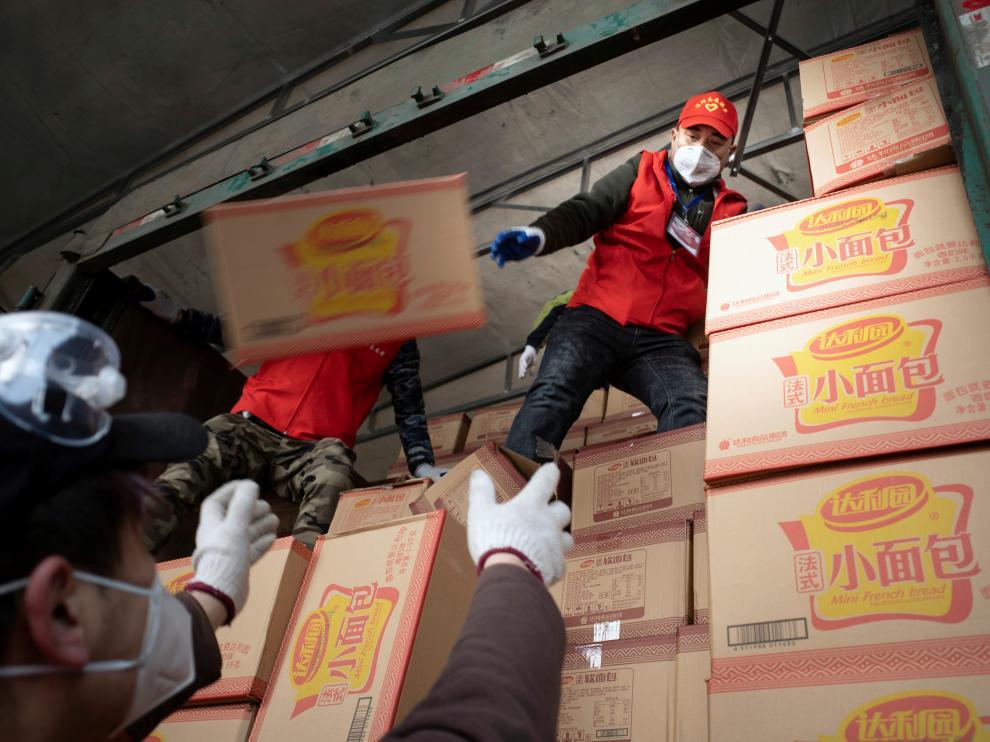 Voluntarios cargan cajas de mascarillas en Xiaogan, en la provincia de Hubei
