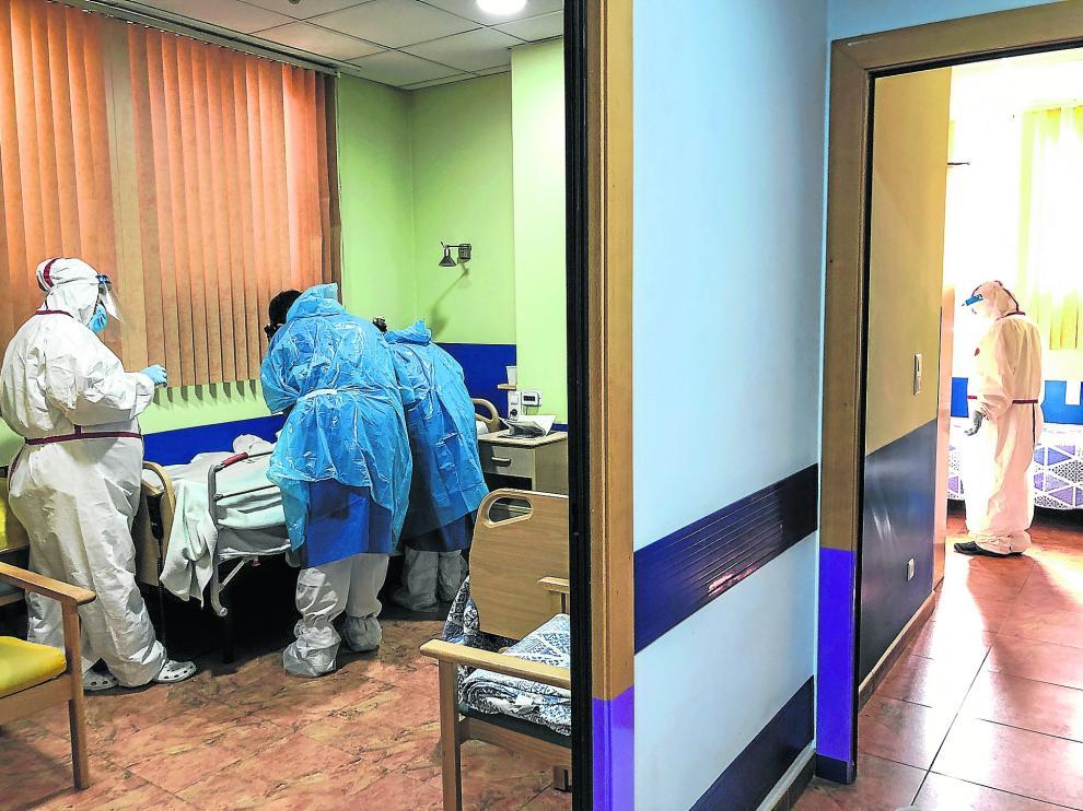 El equipo de EDORE atiende a un paciente con coronavirus acompañado por las gerocultoras de la residencia
