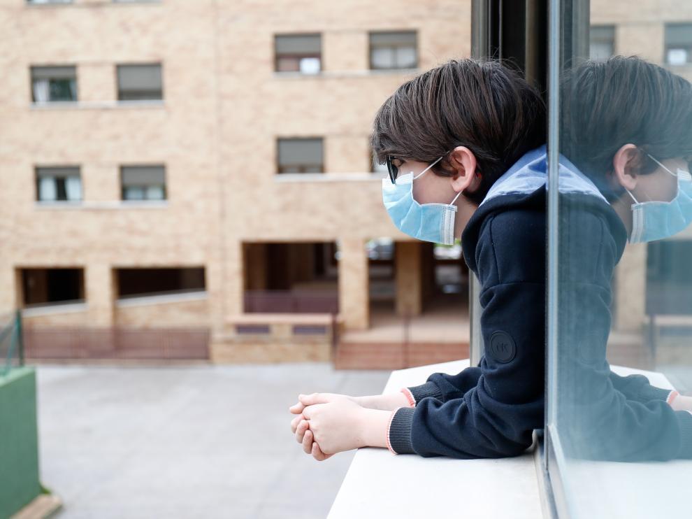 Un niño se asoma a la ventana con mascarilla, en una población de Madrid.