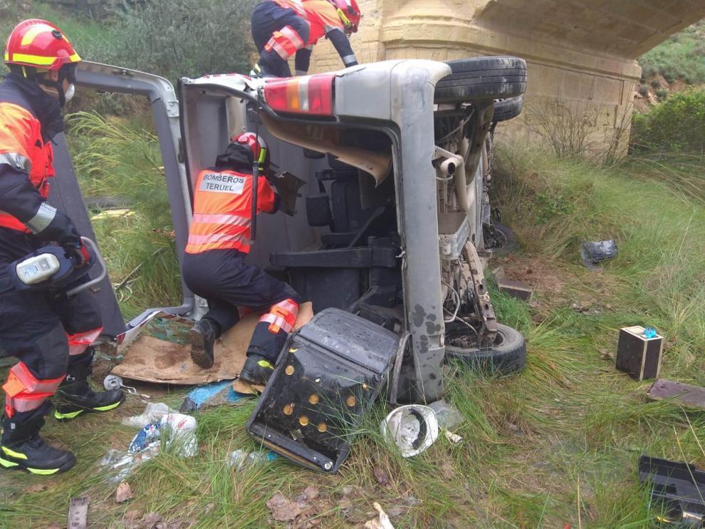 Los bomberos, durante el rescate del conductor herido en Ariño.