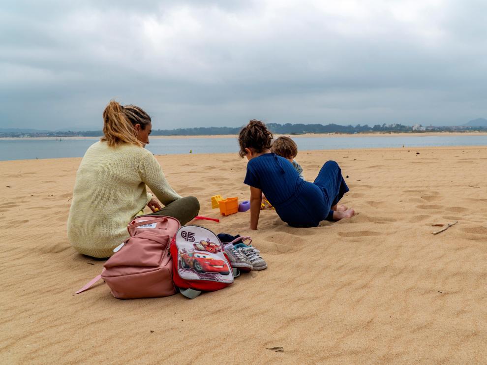 Una mujer con sus dos hijos en la Playa de los Peligros de Santander