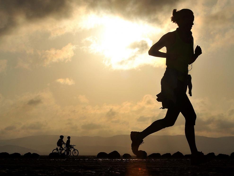 Runners haciendo running montando en bici y corriendo al aire libre