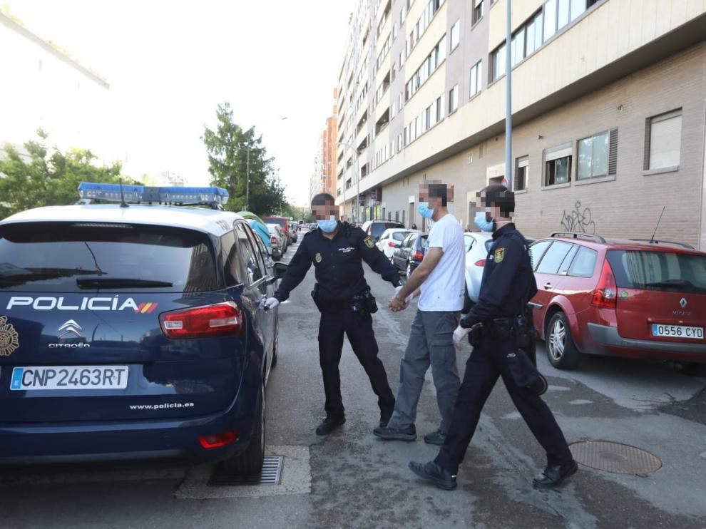 Agentes de la Policía Nacional introducen al guardia civil detenido en el coche patrulla tras registrar su domicilio.