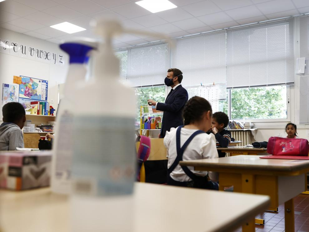 France's President Emmanuel Macron wears a protective face mask with a blue-white-red coloured ribbon as he speaks with schoolchildren during a visit to the Pierre de Ronsard elementary school in Poissy, France, May 5, 2020, as France readies to face an ease in the coronavirus lockdown measures. Ian Langsdon/Pool via REUTERS [[[REUTERS VOCENTO]]] HEALTH-CORONAVIRUS/FRANCE-SCHOOL