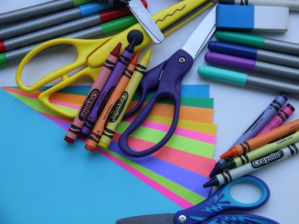 Tijeras, papel y lápices de colores para hacer la manualidad.