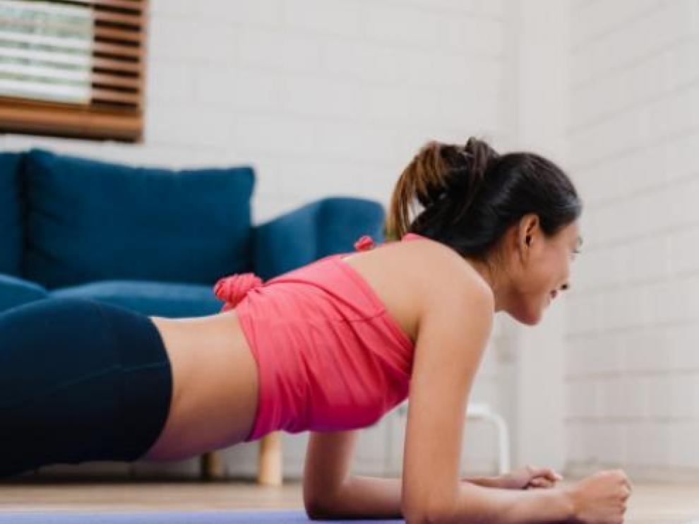 Una mujer haciendo ejercicio en el salón de su casa.