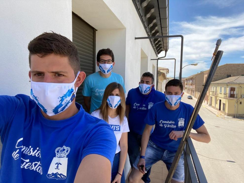 Miembros de la Comisión de Fiestas junto al cohete anunciador y luciendo las mascarillas personalizadas que ha realizado y entregado el Ayuntamiento de Tardienta.
