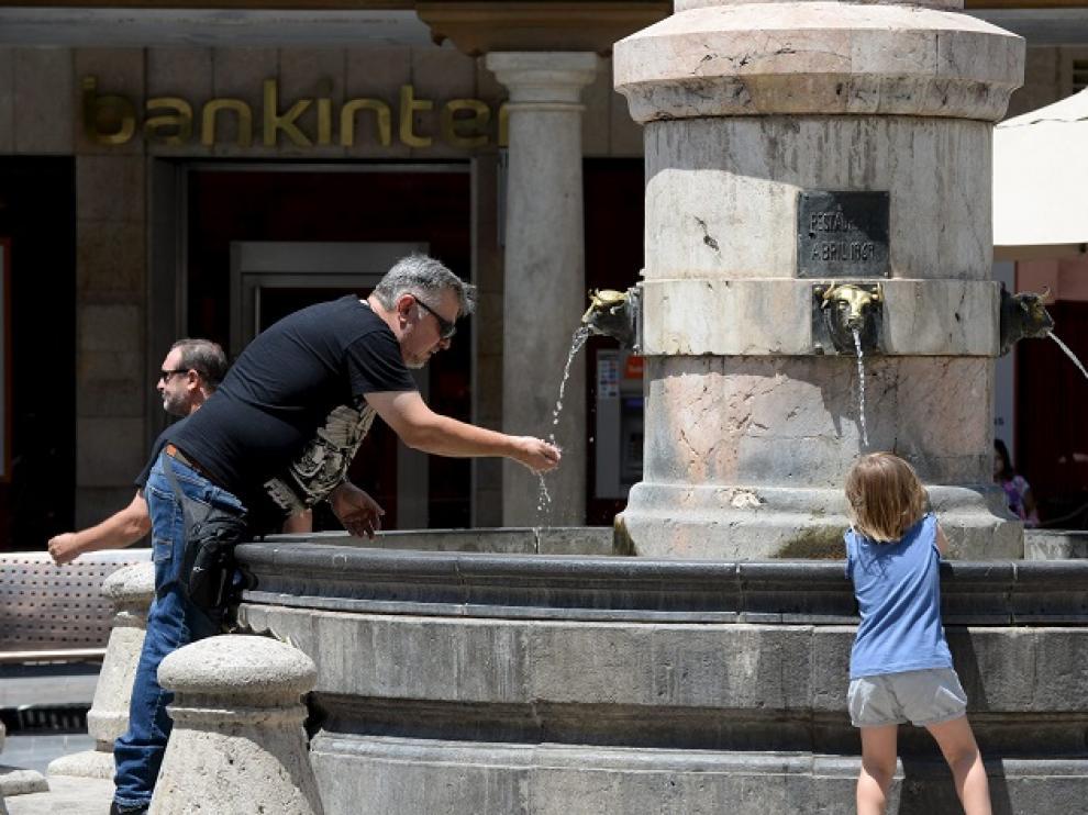 Gente refrescándose en la fuente del Torico de Teruel