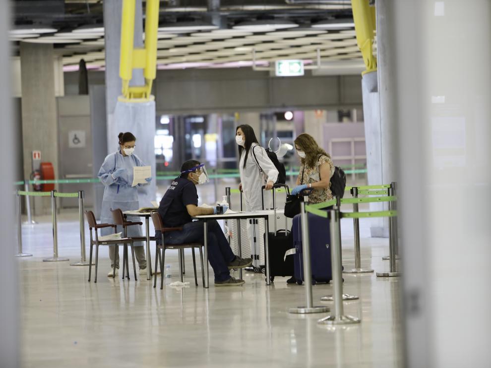 Varios pasajeros llegan al aeropuerto de Barajas procedentes de Colombia este sabado en Madrid.
