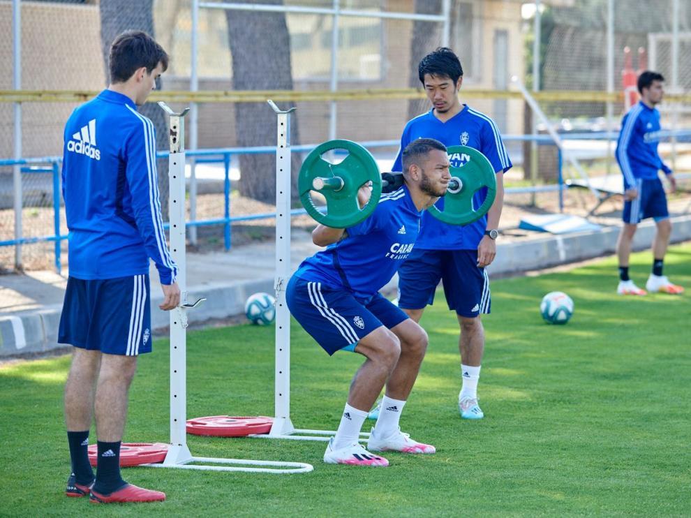 Luis Suárez levanta pesas, ante la mirada de Kagawa y el joven Francho.