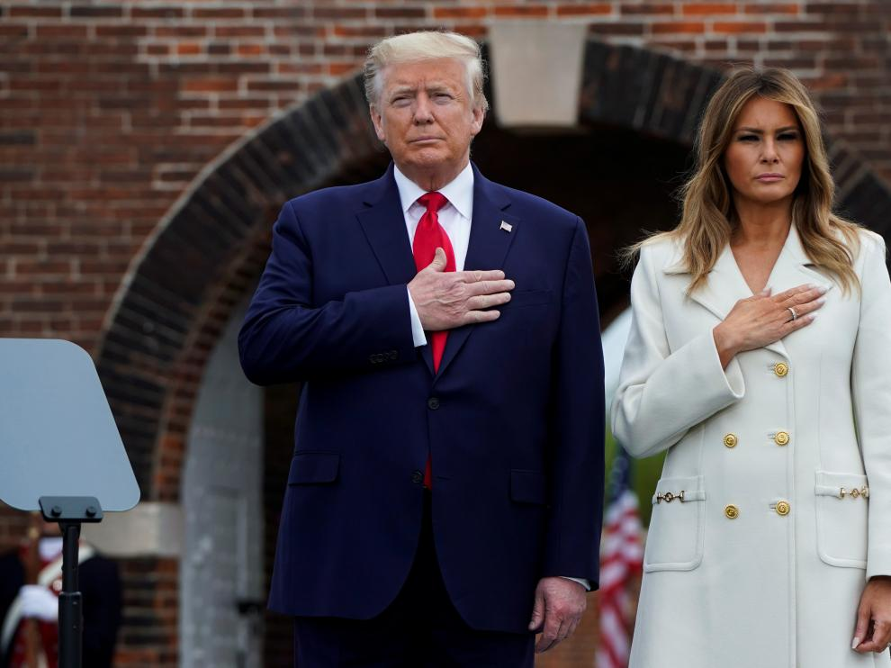 U.S. first lady Melania Trump watches as President Donald Trump salutes while participating in a wreath laying ceremony at the Tomb of the Unknown Soldier at Arlington National Cemetery near Washington in commemoration of the Memorial Day holiday in Arlington, Virginia, U.S., May 25, 2020. REUTERS/Erin Scott [[[REUTERS VOCENTO]]] USA-TRUMP/