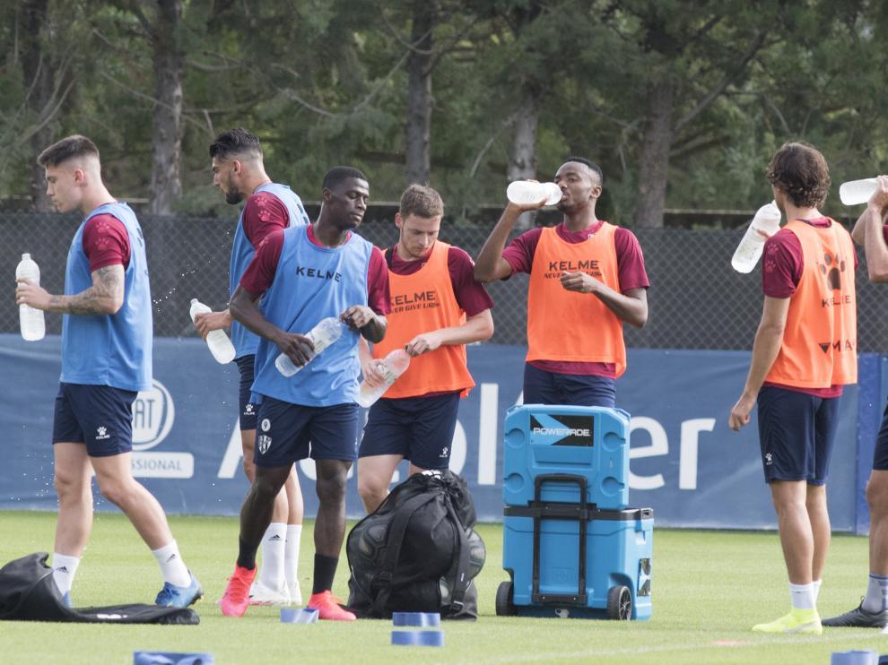 Los jugadores de la SD Huesca se hidratan durante el entrenamiento del miércoles.
