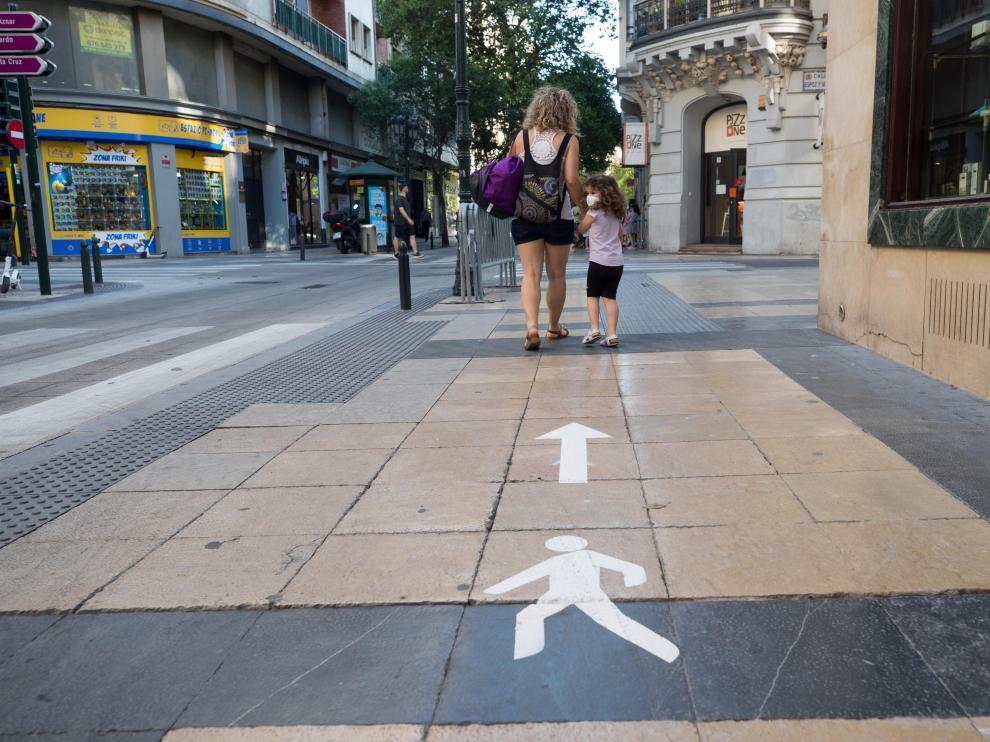 La señalización en las aceras ayuda a los ciudadanos a mantener los dos metros de distanciamiento entre las personas por la calle.