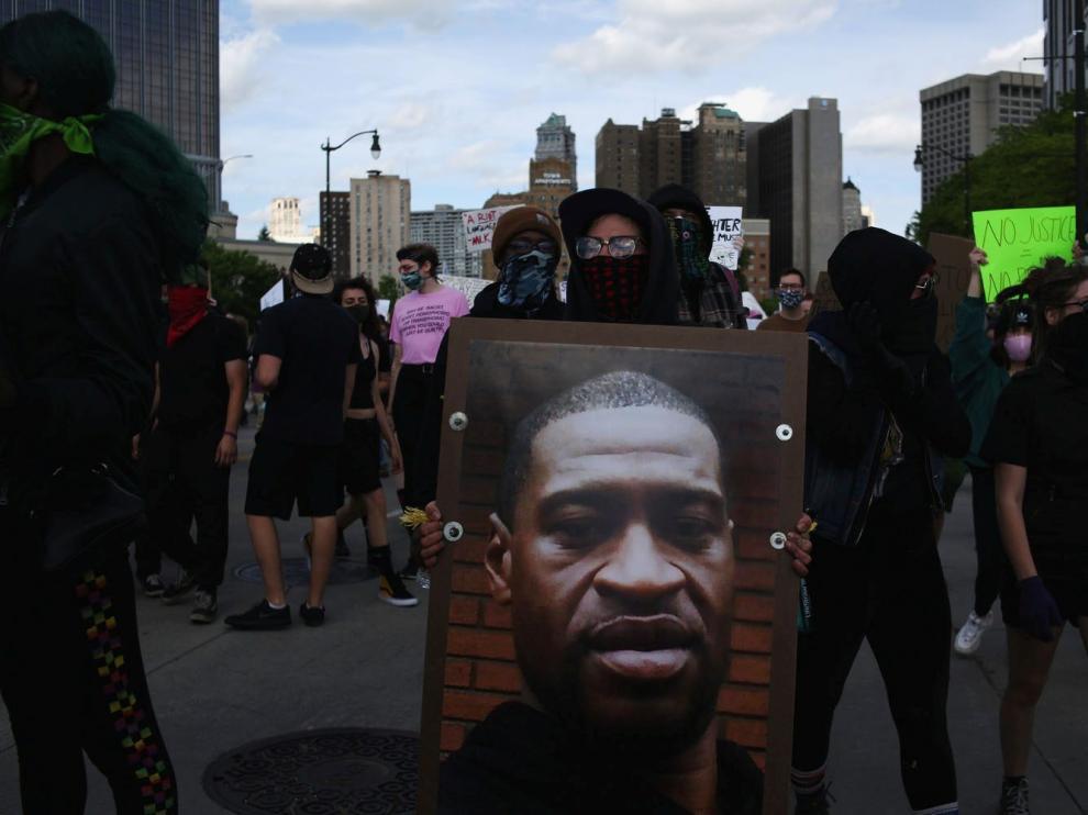 Un manifestante en Detroit con un cartel con el rostro de Georges Floyd, muerto a manos de la Policía,