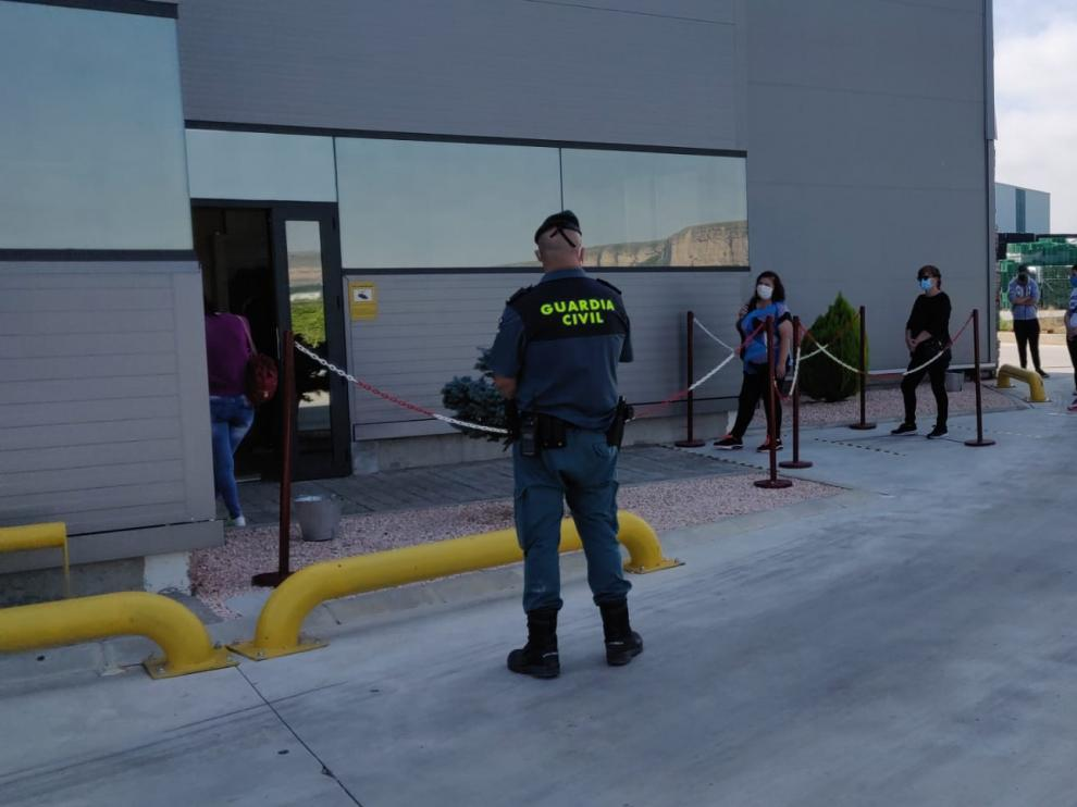 Los trabajadores guardan cola manteniendo la distancia de seguridad frente a las instalaciones de la empresa.