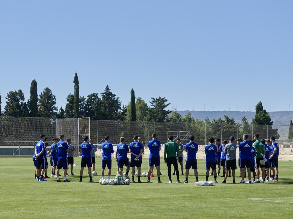 Los futbolistas del Real Zaragoza, en grupo, atiende el discurso de Víctor Fernández.