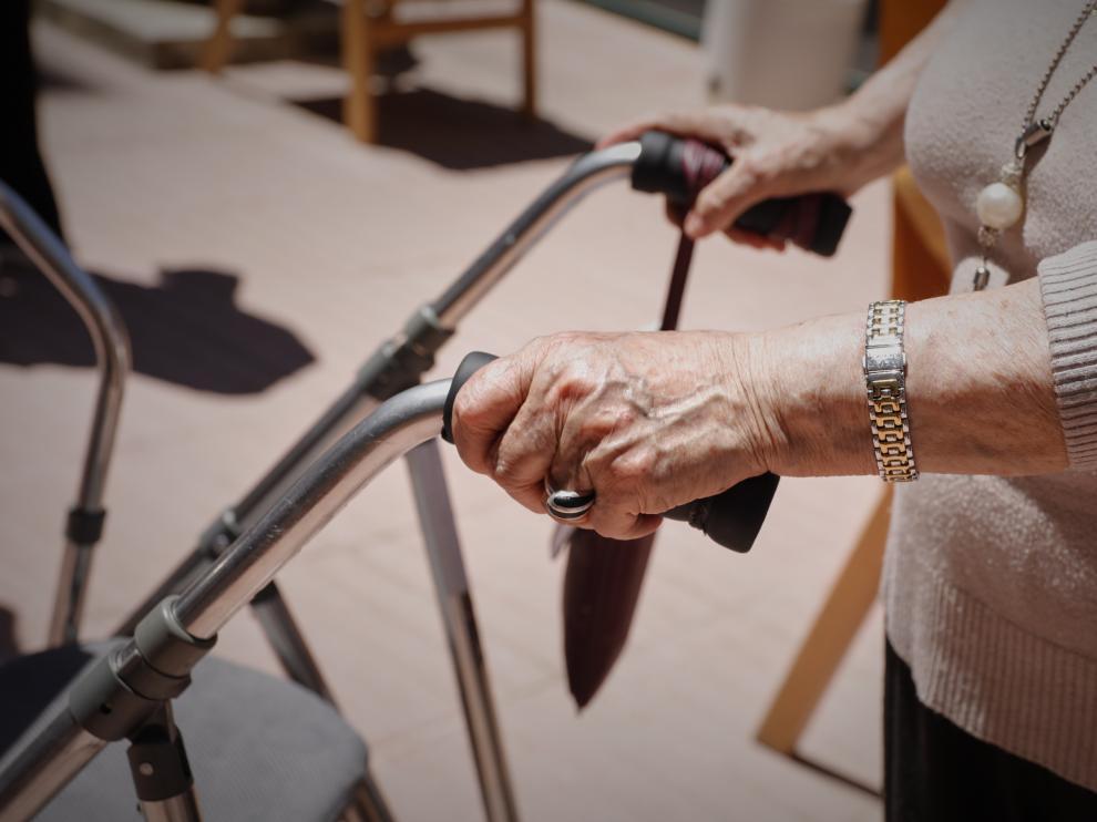 Una anciana con un andador en una residencia.