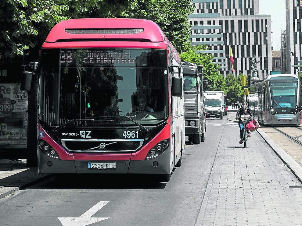 Un autobús y un tranvía, a su paso por el paseo de la Independencia.