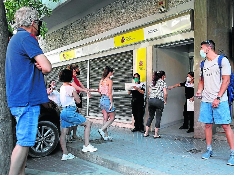 Trabajadores guardan fila ante una oficina del SEPE.