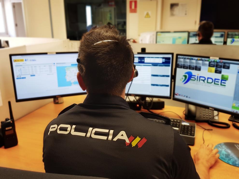 Un agente de la Policía Nacional ante varios ordenadores.