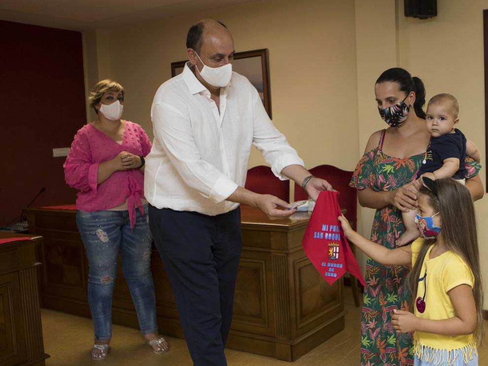 El alcalde de El Burgo de Ebro, Vicente Royo, entrega el pañuelico a una de las familias de la localidad