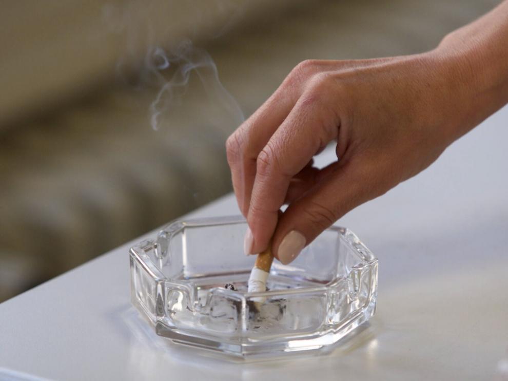 Una fumadora apagando un cigarrillo en un cenicero
