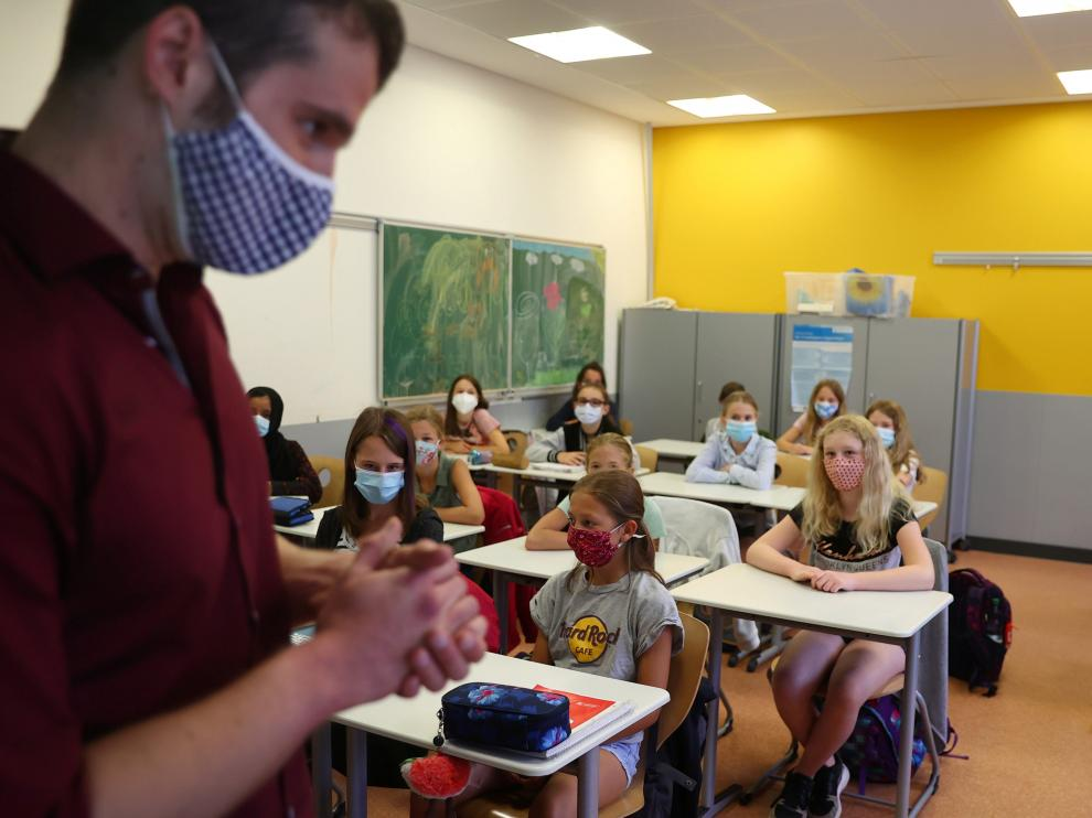 Schoolgirls and schoolboys of the fifth year voluntarily wear protective face masks inside their classroom as schools re-open after summer holidays and the lockdown due to the outbreak of the coronavirus disease (COVID-19) at the Karl-Rehbein high school in Hanau, Germany, August 17, 2020. REUTERS/Kai Pfaffenbach [[[REUTERS VOCENTO]]] HEALTH-CORONAVIRUS/GERMANY-EDUCATION