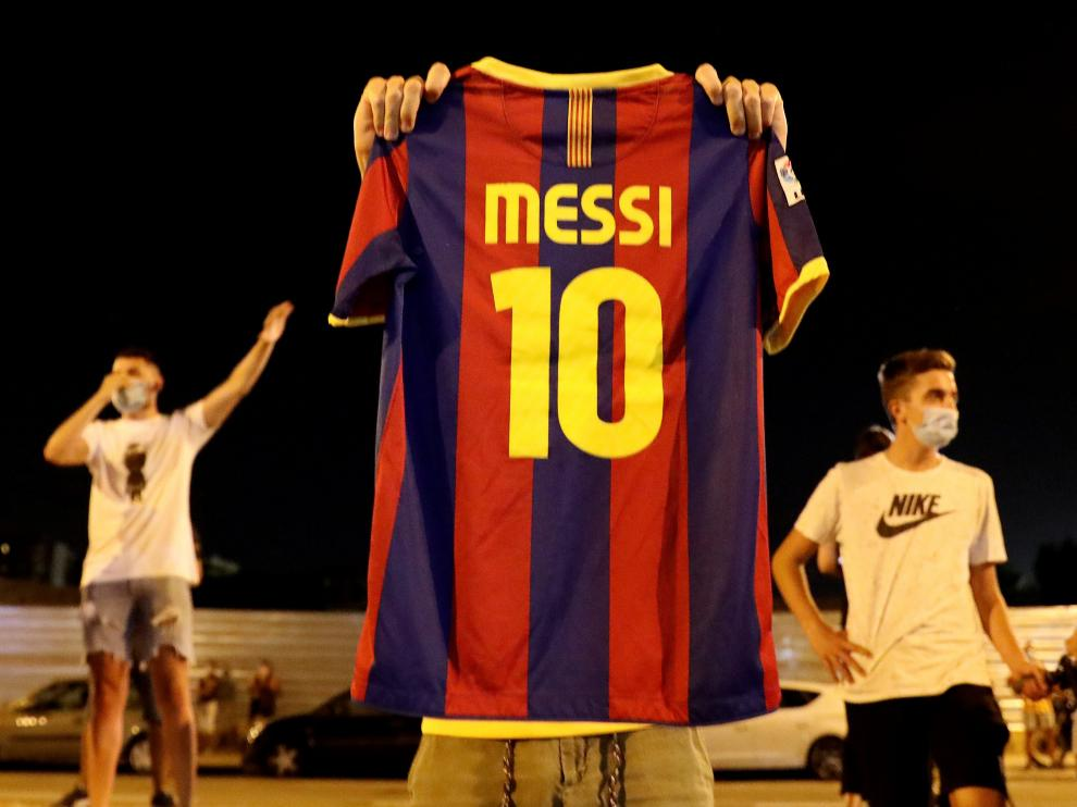 Soccer Football - Camp Nou, Barcelona, Spain - August 25, 2020 A Barcelona fan holds up a Lionel Messi shirt outside the Camp Nou after captain Lionel Messi told Barcelona he wishes to leave the club immediately, a source confirmed on Tuesday REUTERS/Nacho Doce [[[REUTERS VOCENTO]]] SOCCER-SPAIN-FCB/MESSI