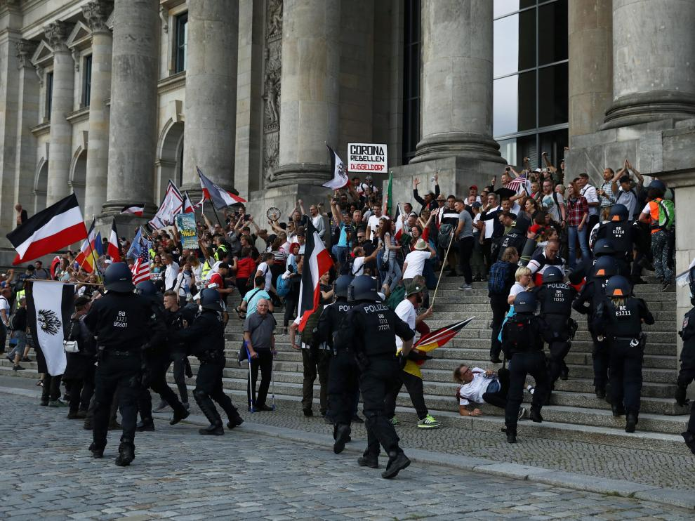 Police officers react in front of the Reichstag Building during a rally against the government's restrictions following the coronavirus disease (COVID-19) outbreak, in Berlin, Germany, August 29, 2020. REUTERS/Christian Mang [[[REUTERS VOCENTO]]] HEALTH-CORONAVIRUS/GERMANY-PROTEST