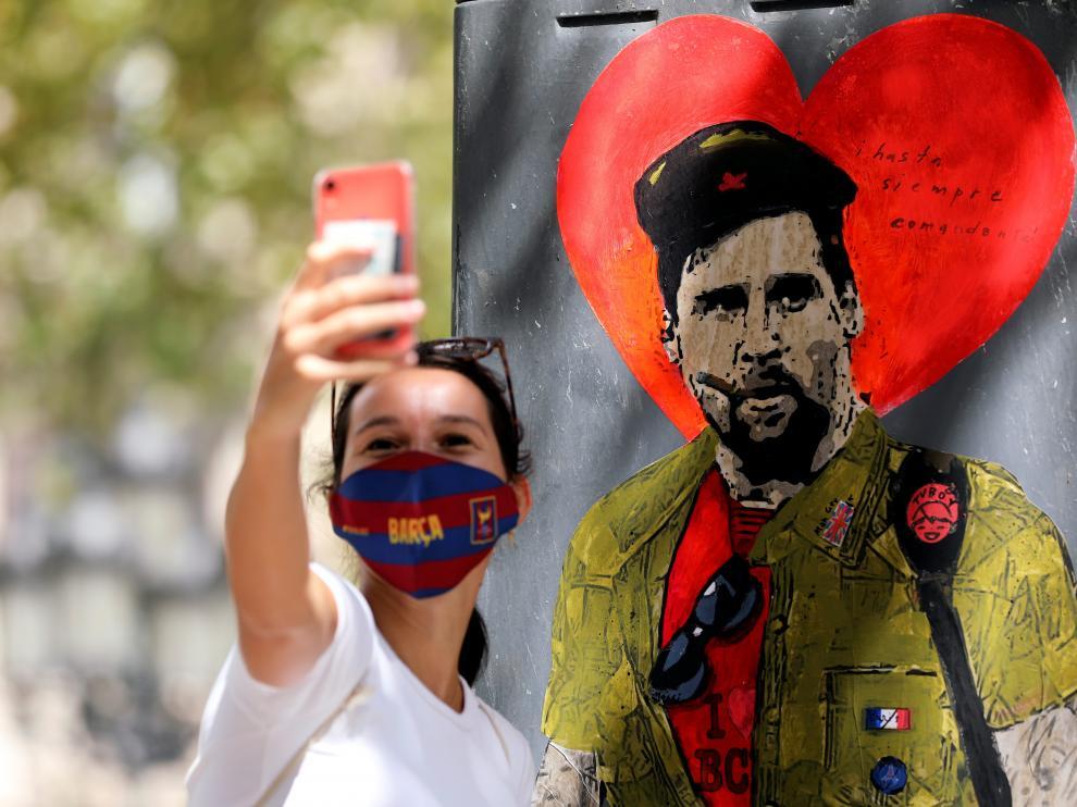 Una mujer se toma un serfi con un mural del astro argentino en Barcelona