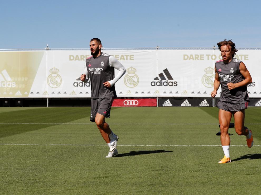 El delantero del Real Madrid Karim Benzema (izquierda) y el centrocampista Luka Modric (derecha) asisten al entrenamiento del equipo en Valdebebas, Madrid, este lunes.