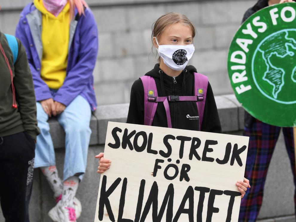 Greta Thunberg sostiene un cartel que dice 'Huelga escolar por el clima' durnate una protesta frente al Parlamento sueco, en Estocolmo.