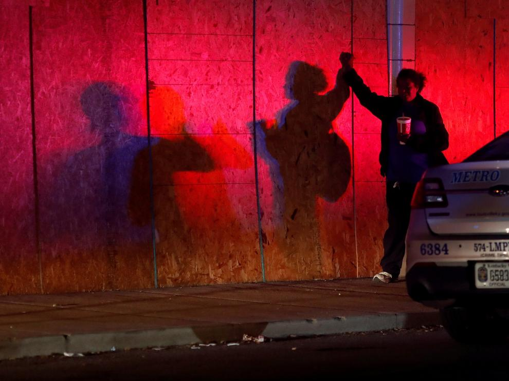 A woman stands by a police vehicle before a 9pm curfew in Louisville, Kentucky