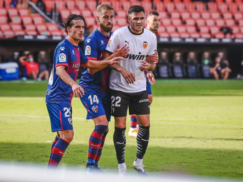 Seoane y Pulido, de la SD Huesca, junto a Maxi Gómez, del Valencia.
