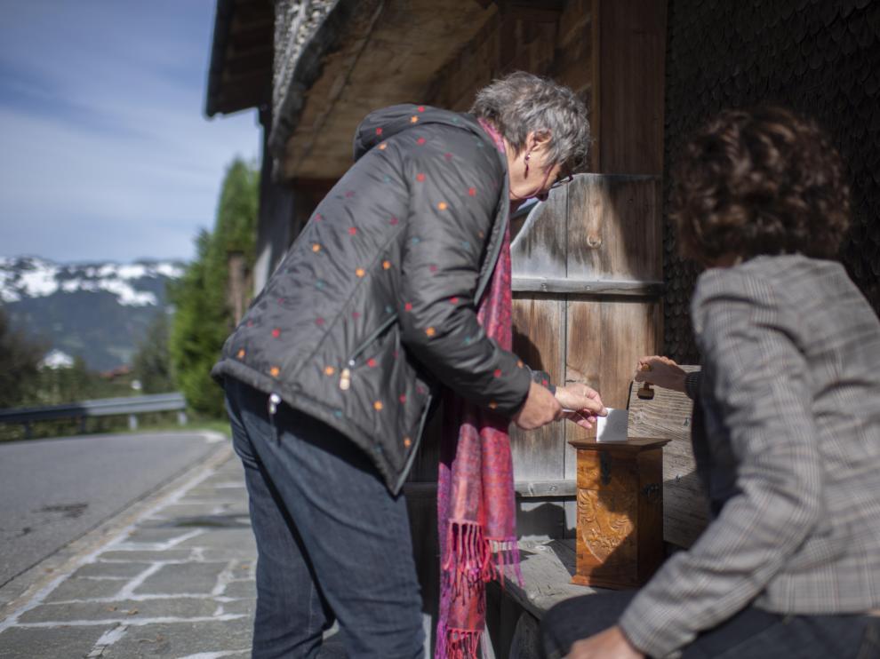Una ciudadana introduce su voto en una urna portátil en una localidad suiza.