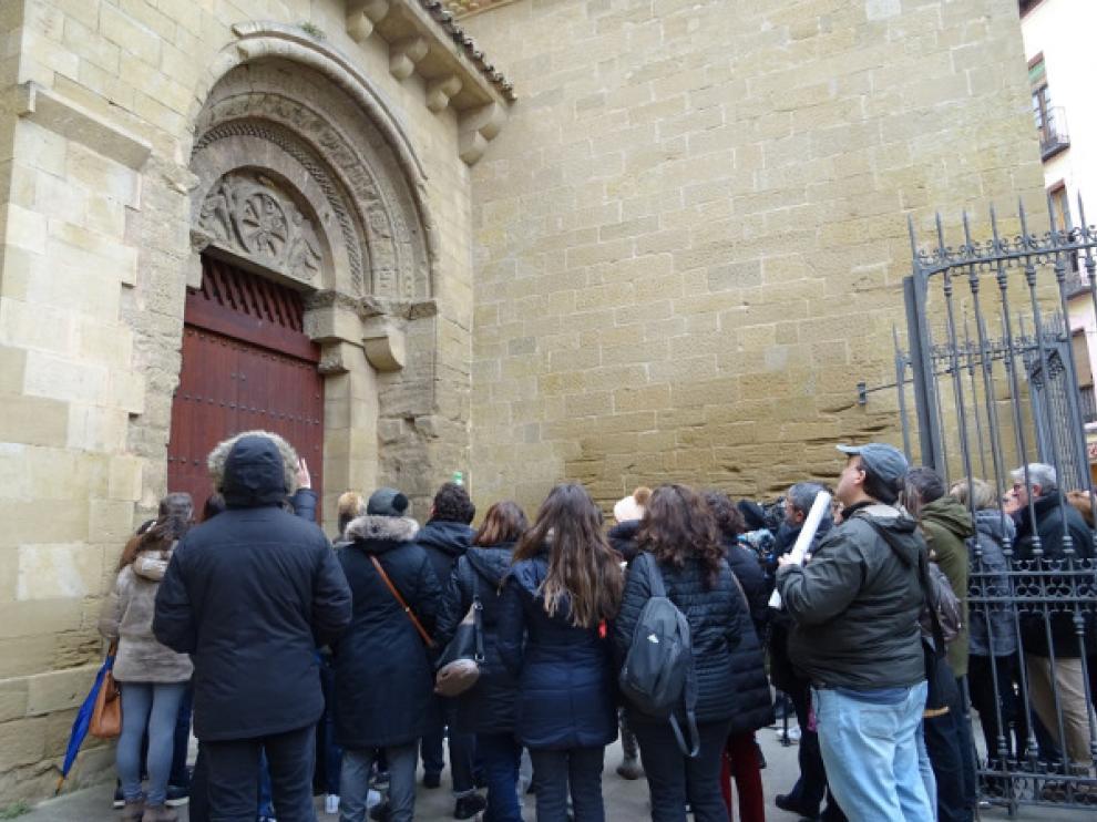 Un grupo de turistas en la entrada de la iglesia de San Pedro, incluida en la visita guiada a Huesca.