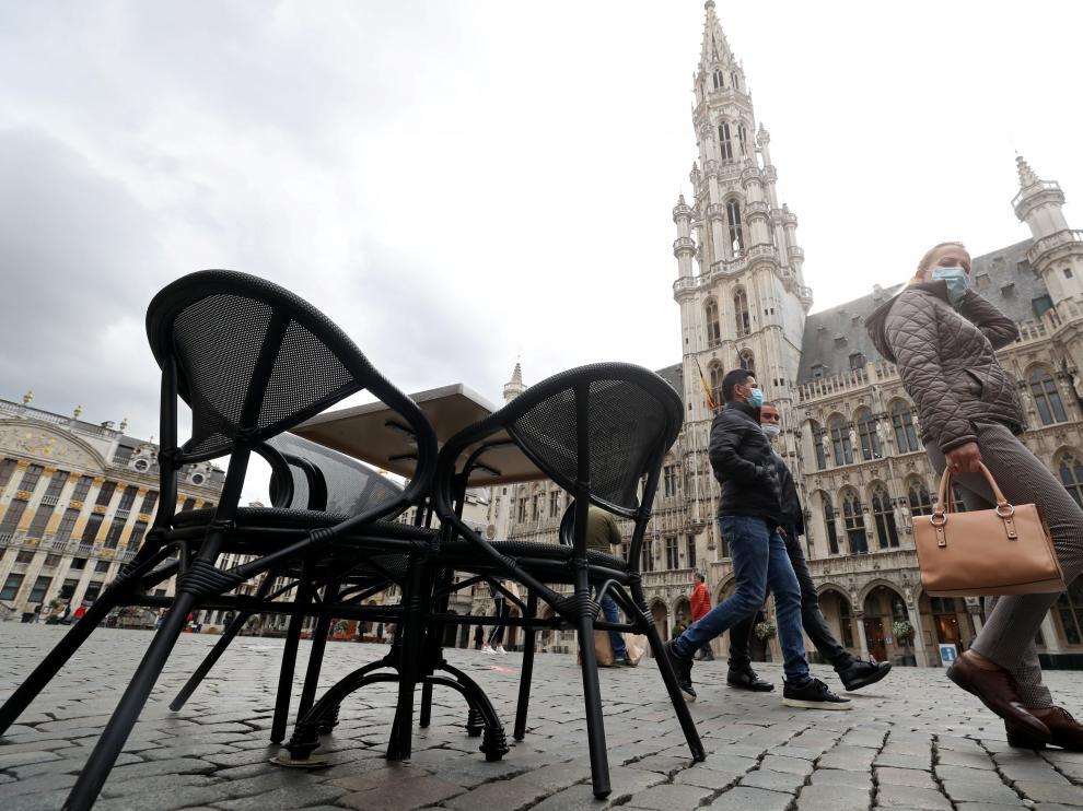 Varias personas pasean por la Grand Place de Bruselas.
