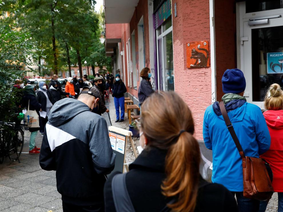 Decenas de personas hacen fila delante de una consulta médica de Berlín para hacerse una prueba PCR.