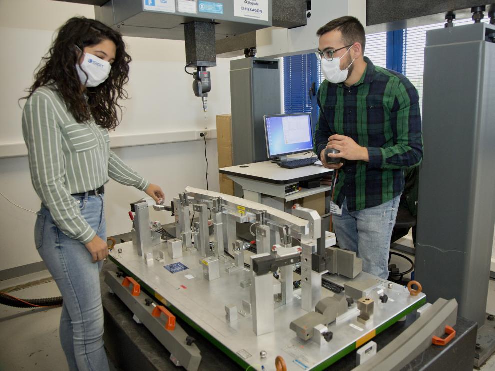 Los ingenieros Silvia Vicén y Pablo Rodríguez, con una de las máquinas para testear piezas