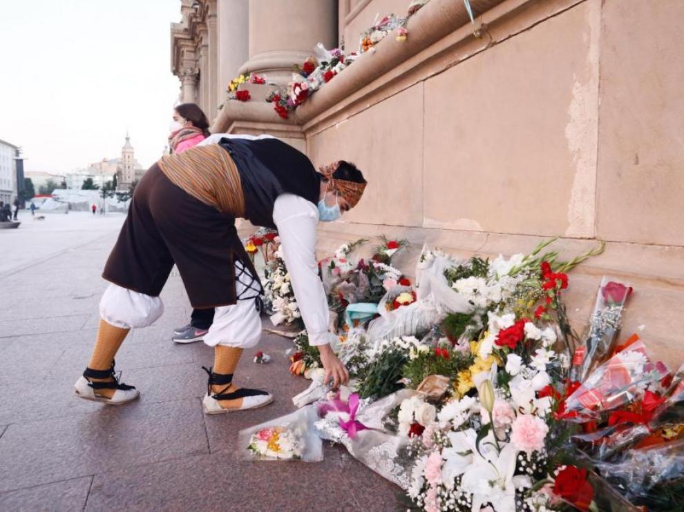 Un hombre vestido con el traje regional aragonés deposita un ramo de flores en la plaza del Pilar.