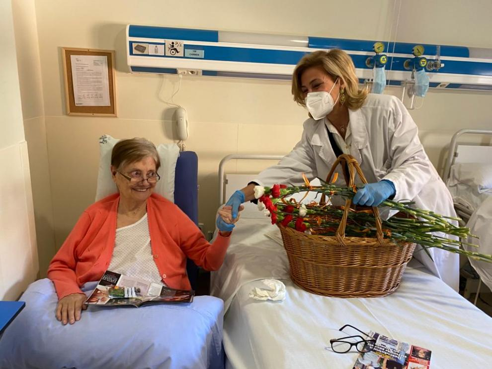 Una paciente ingresada en el Hospital San Juan de Dios recibe un clavel.