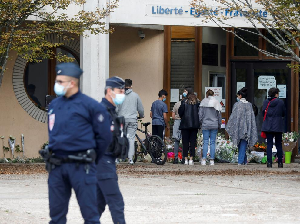 Varias personas depositan flores en la entrada del colegio donde daba clase el profesor asesinado.