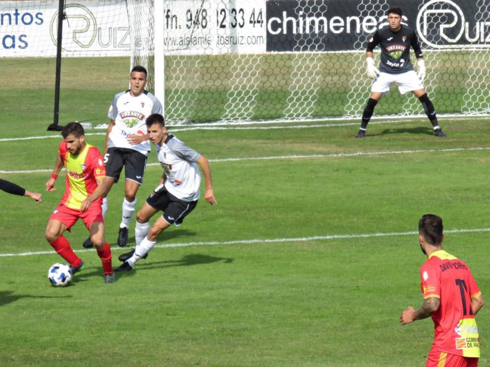 Un jugador del Ejea conduce el balón ante la presión de un defensa rival.
