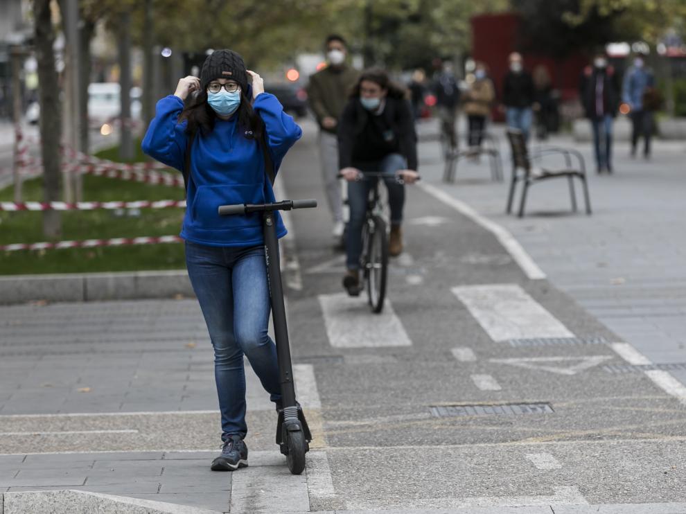 Una usuaria de patinete espera en un semáforo del carril bici de Fernando el Católico.