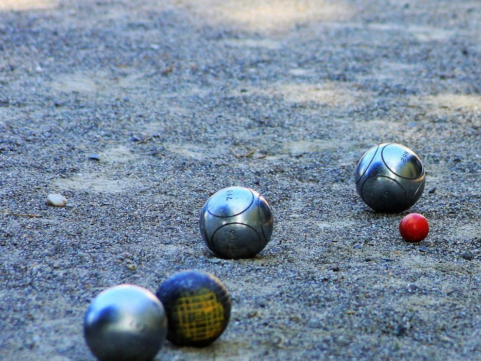 la petanca es un juego tradicional en el que el objetivo es lanzar bolas metálicas tan cerca como sea posible de una pequeña bola de madera